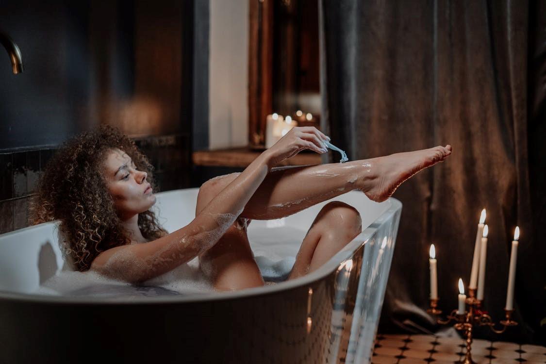 A woman shaving her legs while taking a bath