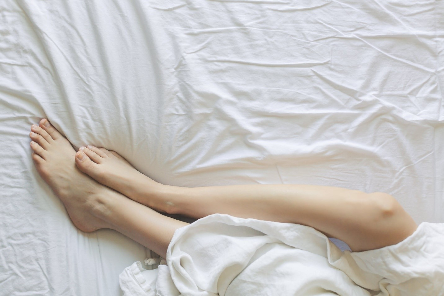 A woman with silky smooth hairless skin lying in bed