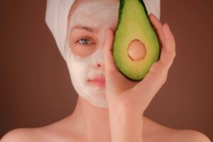 woman with facial holding an avocado to her face
