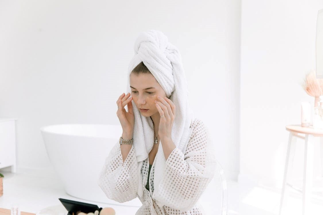A woman in a bathrobe touching her face