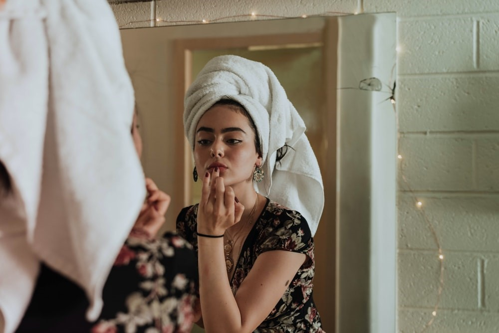 woman looking in the mirror and applying products
